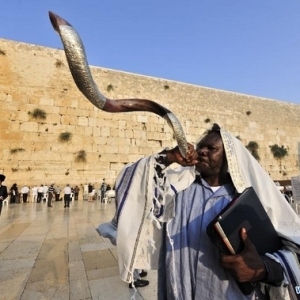 A JEW BLOWING THE SHOFAR AT THE WAILING WALL.
