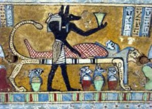 PRIEST OF ANUBIS IN ANCIENT EGYPT DEPICTED HERE WEARING AN ANUBIS MASK, PREPARING THE BODY OF THE DEAD BY EMBALMING IT FOR THE AFTERLIFE.